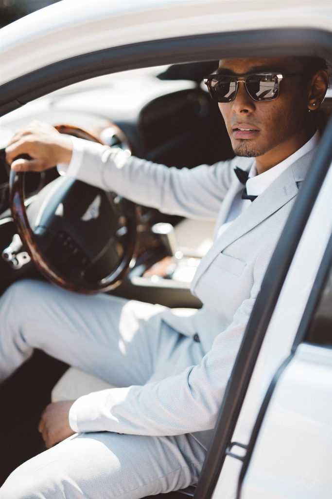 Beau garçon métissé au volant d'un Bentley Continental